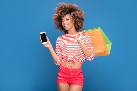 Happy african american woman holding colorful shopping bags and showing mobile phone with empty screen, smiling, posing on blue background.
