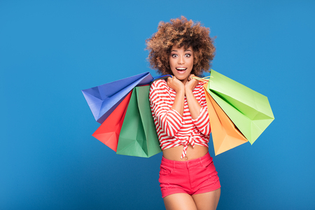 Happy african american woman holding colorful shopping bags, smiling, posing on blue background. Shopaholic content.