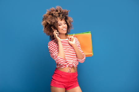 Happy african american woman holding colorful shopping bags and talking by mobile phone , smiling, posing on blue background.