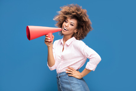 Smiling beautiful young African American woman with curly afro hair screaming by megaphone. Stock Photo