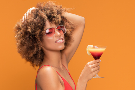 Photo of an excited african girl dressed in red swimsuit posing with colorful drink , isolated over yellow background.