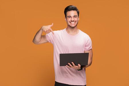 Happy handsome young man holding laptop computer, posing over orange studio background.