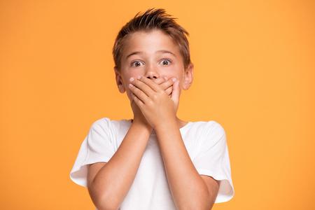 Jonge emotionele knappe jongen die zich op oranje studioachtergrond bevindt. Menselijke emoties, gezichtsuitdrukking concept. Stockfoto
