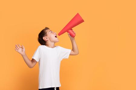Little handsome boy with red megaphone on orange studio background.