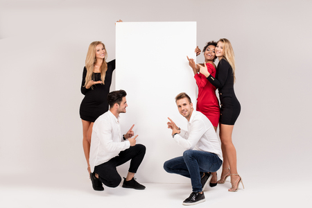 Group of young multi-ethnic beautiful people wearing elegant clothes posing together with empty white board. Cheerfull smiling friends.