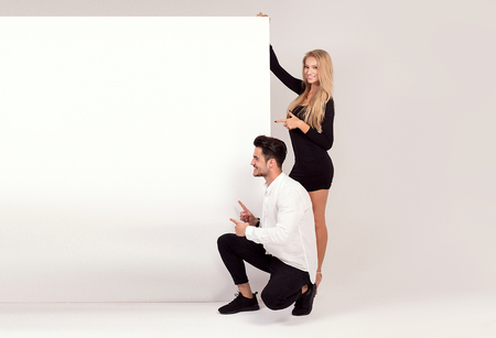 Happy young couple holding white banner with copy space. Man and woman with blank board.