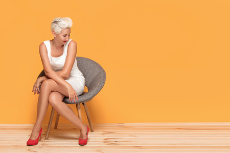 Beautiful middle aged blonde lady smiling, relaxing. Woman wearing red fashionable high heels posing on yellow studio background. Foto de archivo - 106129460