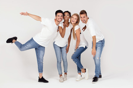 Group of young multi-ethnic attractive people wearing white shirts, smiling and having fun together, posing in studio.