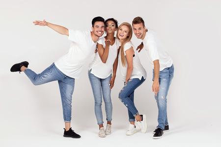 Grupo de jóvenes atractivos multiétnicos vestidos con camisas blancas, sonriendo y divirtiéndose juntos, posando en el estudio.