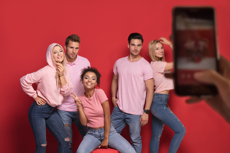 Group of young people enjoy their company, smiling, having fun together, taking photos by mobile phone.