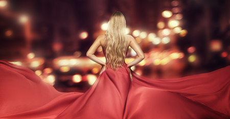 Blonde woman in red fashionable elegant dress. Rear view, back side. City lights on the background.