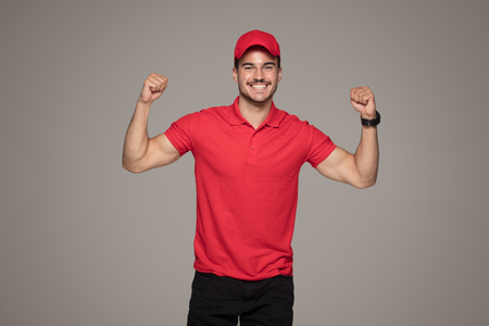 Delivery Concept - Smiling Caucasian courier man posing on studio background.