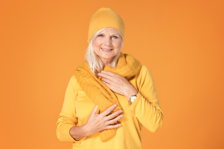 Smiling mature woman in yellow cap and scarf. Studio shot.