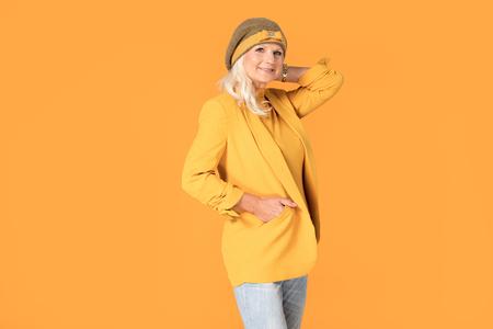 Sonriente mujer madura en boina amarilla posando en estudio. Foto de archivo