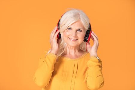 Senior beautiful woman listening to her favorite music through big red headphones, enjoying the sound.