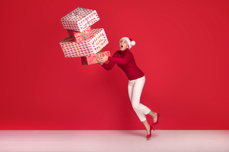 Mature woman in red santa claus hat trying to hold stack of gift boxes, on red studio background. Christmas shopping, copy space. Stock Photo