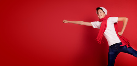 Happy teenager boy jumping in Santa hat smiling and posing on red background.
