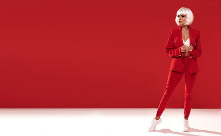 Fashion photo of beautiful woman in white wig and red suit.