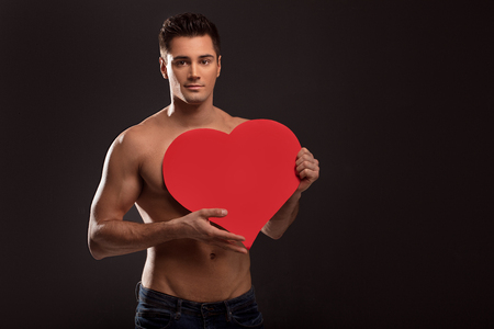 Handsome shirtless man posing with red heart, valentine's day.