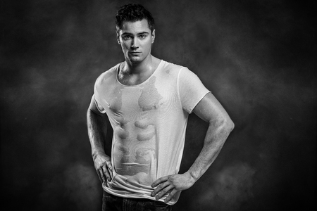 Handsome muscular man posing in wet shirt, looking at camera. Stock Photo
