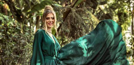 Sensual beautiful woman posing in green maxi dress over tropical plants.