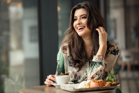 Portrait of attractive lady drinking coffee and eating breakfast at cafeteria.
