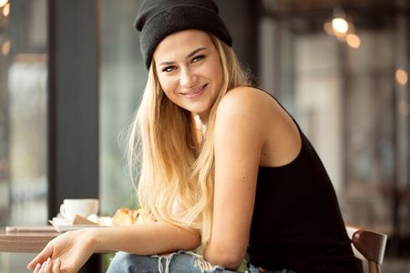 Positive smart student girl eating in restaurant.  Young woman wearing casual cap, smiling.