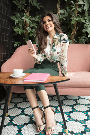 Young beautiful woman holding coffee cup and using mobile phone, sitting at cafeteria. Happy student girl using smartphone. Businesswoman drinking coffee and smiling.