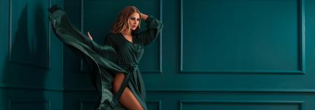 Mode mooie elegante vrouw poseren in groene maxi jurk. Stockfoto