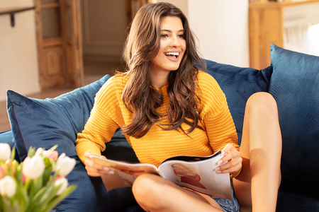 Happy attractive woman reading magazine and drinking coffee at home, morning time. Daily lifestyle.