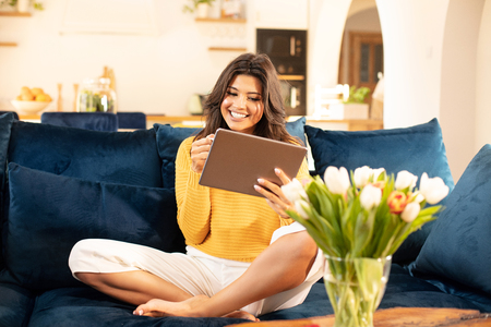 Young Smiling Woman looking at Tablet, Relaxing on Sofa. Relaxation and daily lifestyle Concepts.