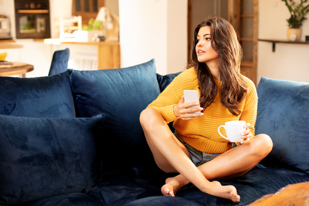 Beautiful young woman relaxing at home with cup of coffee and mobile phone in hand.