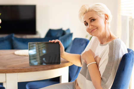 Beautiful blonde woman using digital tablet, showing on empty screen. Smiling lady browsing internet over tablet at home. Middle age woman smiling to the camera. Archivio Fotografico - 124694901