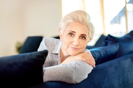 Portrait of natural middle aged woman relaxing at home, looking at camera.