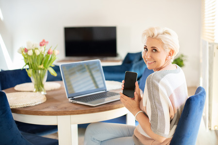 Beautiful blonde woman using laptop and mobile phone , showing empty screen. Happy lady working in home office. Middle age woman smiling to the camera. Archivio Fotografico - 124694741