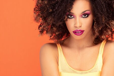 Beautiful young african american woman with afro hairstyle and glamour makeup posing in studio, looking at camera. Colorful photo. Orange background. Beauty shot.