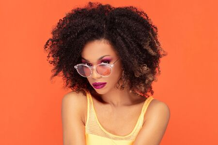 Beautiful young african american woman with afro hairstyle and glamour makeup posing in studio, looking at camera, wearing fashionable sunglasses. Colorful photo. Orange background. Beauty shot.