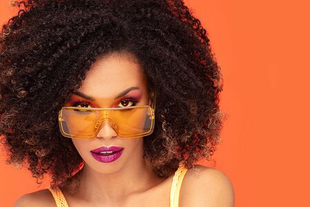 Beautiful young african american woman with afro hairstyle and glamour makeup posing in studio, looking at camera, wearing fashionable sunglasses. Colorful photo. Orange background. Beauty shot. Banco de Imagens - 128584947