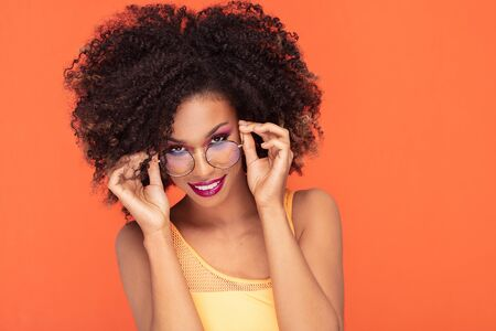 Beautiful young african american woman with afro hairstyle and glamour makeup posing in studio, wearing fashionable eyeglasses. Colorful photo. Orange background. Beauty shot.