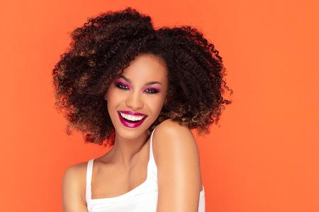 Feliz mujer sonriente con maquillaje glamour. Foto de joven africana sobre fondo naranja.