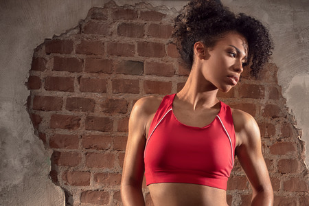 Photo of sport young woman with afro hairstyle after gym workout.