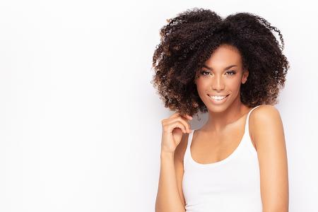 Jonge modieuze afro meisje poseren in wit overhemd, glimlachend naar de camera. Witte studioachtergrond. Stockfoto