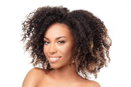 Retrato de belleza de mujer afroamericana con piel limpia y sana sobre fondo blanco. Concepto de belleza y cuidado de la piel. Sonriente hermosa niña afro. Foto de archivo