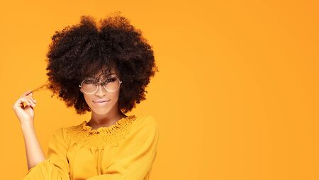 Happy african american woman smiling. Young emotional afro woman wearing fashionable eyeglasses and yellow dress.