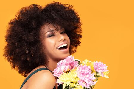 Beauty portrait of african american woman with glamour makeup and fresh flowers in hand posing on yellow studio background.