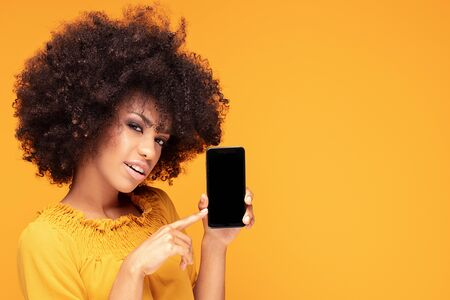 Excited african american girl hold mobile phone with blank empty screen isolated on yellow studio background . Emotions, lifestyle concept. Copy space. Imagens