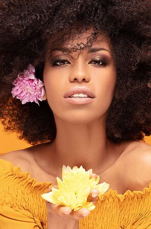 Beauty portrait of african american woman with glamour makeup, afro hair and fresh flowers in hand posing on yellow studio background.