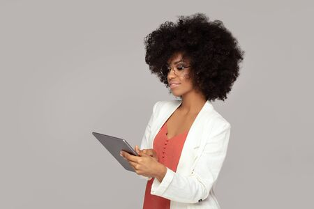 Young Happy African American Woman Using Digital Tablet Isolated on a grey background.