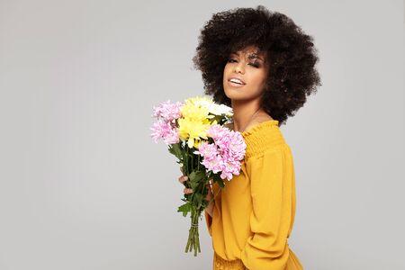 Jeune belle femme afro tenant des fleurs fraîches, souriant à la caméra.