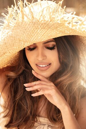 Beauty portrait of young attractive girl wearing straw hat, smiling, enjoying sunny weather.